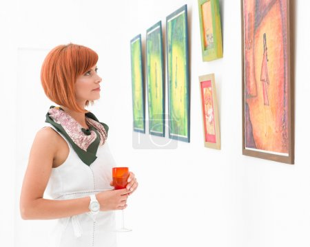 Photo for Young caucasian redhead woman standing in a museum admiring colorful framed paintings - Royalty Free Image