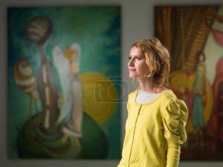 Photo pour Vue latérale de belle femme caucasienne contemplant des œuvres d'art dans un musée d'art - image libre de droit