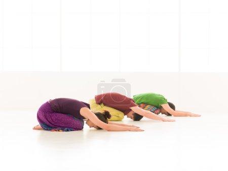 Photo pour Trois jeunes une femme et deux hommes pratiquent le yoga en classe sur fond vitré coloré - image libre de droit
