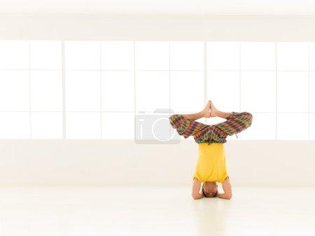 Photo pour Gros plan de jeune homme célibataire en posture de yoga avancée, habillé coloré, en studio gym - image libre de droit