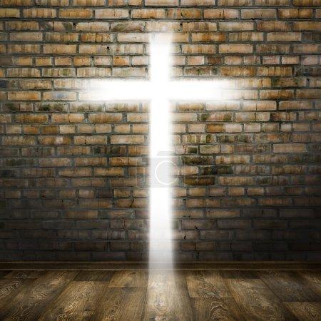 Photo pour Lumière du trou croix dans la pièce sombre avec mur de briques et plancher de bois - image libre de droit