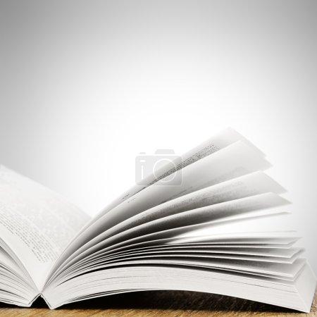 Photo pour Ouvrir le livre sur la table en bois sur fond blanc. avec la place pour le texte - image libre de droit