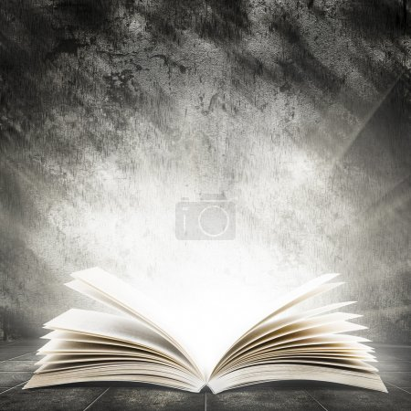 Old open book with magic light on a dark abstract ...