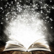Old open book with magic light and falling stars o...
