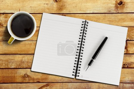 Photo for Notebook with pen and cup with coffee on wood table background, close-up - Royalty Free Image