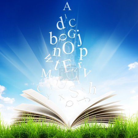 Photo for Open book with flying letters in green grass over blue sky background. Magic book - Royalty Free Image