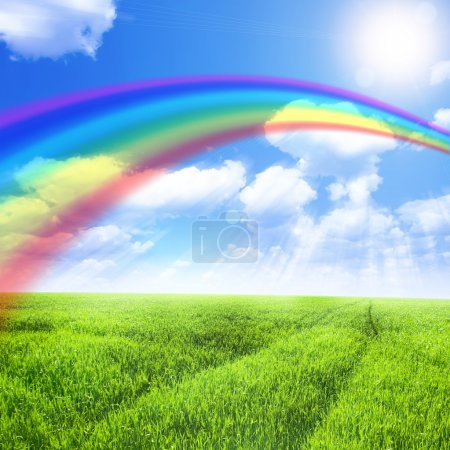 Photo for Green field under blue sky with sun and rainbow - Royalty Free Image