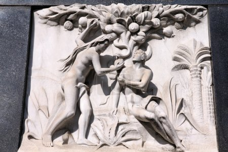 Photo for Milan, Italy. Old biblical scene sculpture at the Monumental Cemetery (Cimitero Monumentale). Religious art depicting Adam and Eve picking the fruit in the garden of Eden. - Royalty Free Image