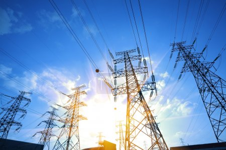 Photo for High-voltage power transmission towers in sunset sky background - Royalty Free Image