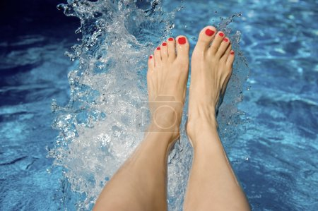 Photo pour Les jambes des femmes éclaboussant dans une piscine - image libre de droit
