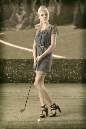 Photo for Beautiful blonde girl in full lenght plays golf with blue short dress and hig shoes, vintage color shot - Royalty Free Image