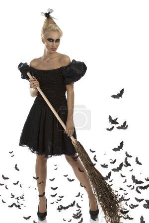 Photo pour Jolie fille blonde avec robe gothique, maquillage sombre et besom, elle prend le besom avec les deux mains et regarde dans la lentille - image libre de droit
