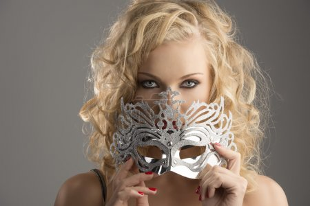 blonde girl with silver mask looks in to the lens