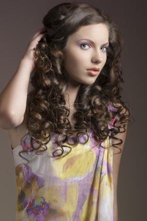 Photo pour Belle brune aux cheveux bouclés et singulet coloré, elle regarde dans la lentille et sa main droite est dans les cheveux - image libre de droit