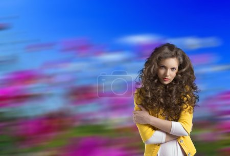 Photo for Pretty brunette with wavy and volume hair wears blue jeans and jellow jacket, she looks in to the lens with crossed arms - Royalty Free Image