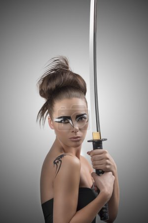 brunette in japan style with katana looka in to the lens