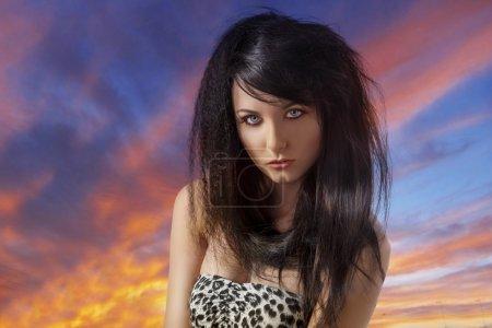 Photo pour Jolie brune aux cheveux longs, jean bleu et t-shirt léopard, elle est devant la caméra et regarde vers l'objectif - image libre de droit