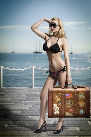 Sexy blonde tourist with vintage bag