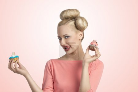 Photo for Pretty blonde girl with creative hair-style and colourful make-up taking two sweets cupcakes and looking in camera - Royalty Free Image