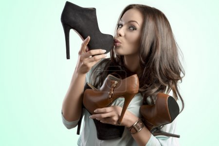 Photo for Funny portrait of pretty brunette girl with many heels in her hands in the sales season. She kissing one shoes - Royalty Free Image