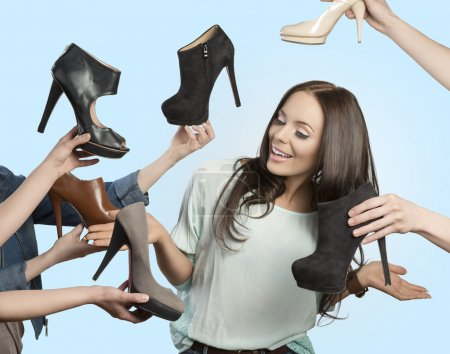 Photo for Funny portrait of smiling fashion brunette woman with long hair surrounded by many elegant shoes - Royalty Free Image