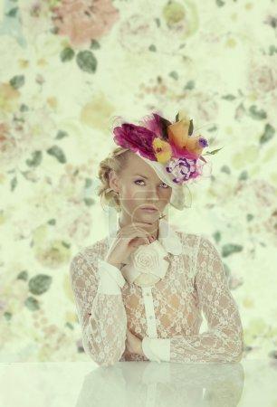 Photo pour Jolie fille derrière la table avec chemise vintage et fleurs sur le chapeau, elle regarde dans la lentille et la main droite est sous le menton - image libre de droit