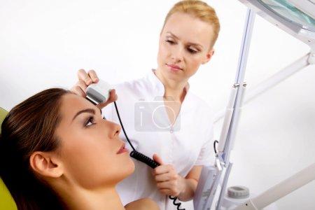 Photo pour Portrait d'attrayante beau jeune brune femme adulte ayant un traitement facial stimulant d'un thérapeute sur la table en spa clinique proffessionel - image libre de droit