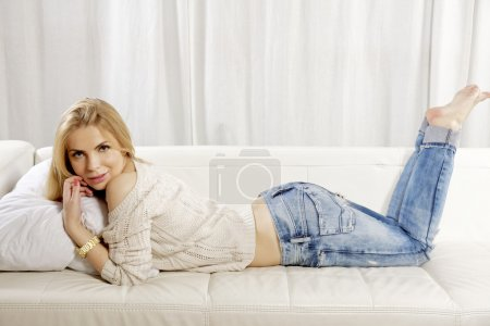 Beautiful and attractive blonde woman posing in blue jeans dress