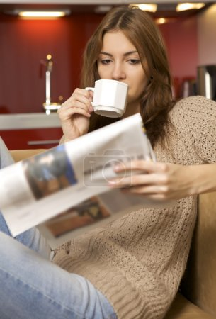 Photo for Mid adult beautiful woman drinking coffee and reading news - Royalty Free Image