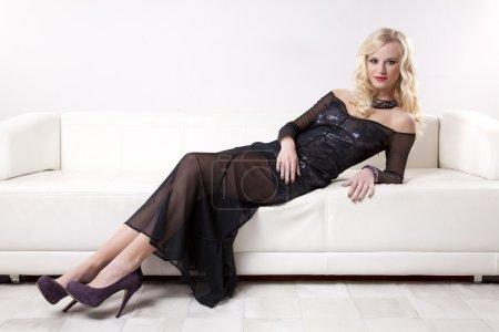 Photo pour Belle et sexy jeune blonde femme adulte robe élégance fashiontable dans le canapé blanc - image libre de droit