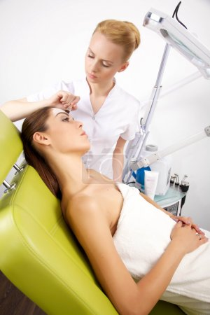 young woman getting beauty skin mask treatment on her face with
