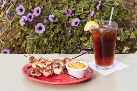 Photo for Grilled chicken skewers served on a red plate with a mango salsa - Royalty Free Image