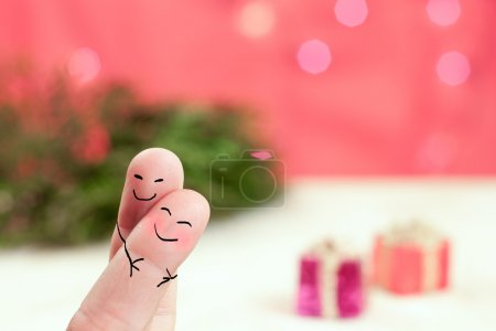 Photo for Hugging fingers with a holiday background with red, green and presents - Royalty Free Image
