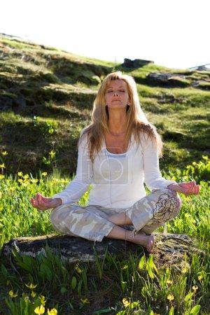 Photo pour Belle femme méditant assise sur un rocher en plein air par un bel après-midi de printemps - image libre de droit