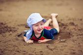 petit garçon souriant dans la flaque de boue