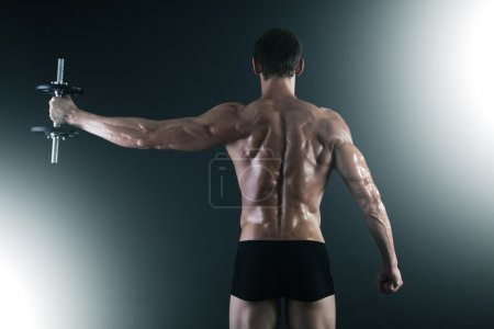 Back of young male bodybuilder doing weight exercise