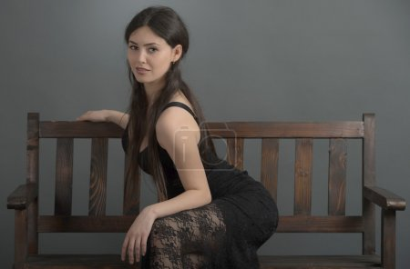 beautiful woman in elegant dress posing in studio sitting on ben