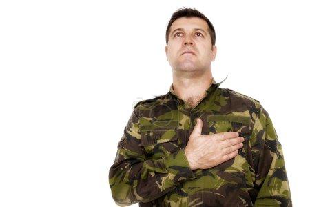 Armeesoldat schwört feierlich mit der Hand auf dem Herzen isoliert auf weiß