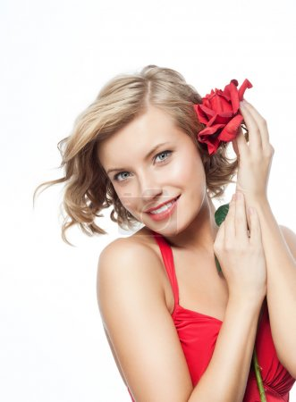 Photo for Portrait of attractive caucasian smiling blond woman isolated on white. Studio shot in red dress with rose - Royalty Free Image