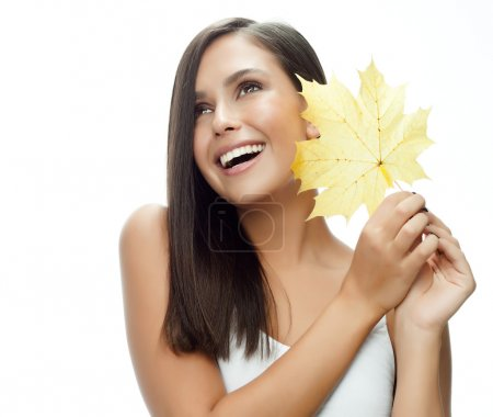 Foto de Retrato de atractiva mujer caucásica sonriente aislado en blanco estudio disparo con hoja de otoño amarillo - Imagen libre de derechos