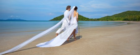 Photo for Beautiful couple on the beach in wedding dress running - Royalty Free Image