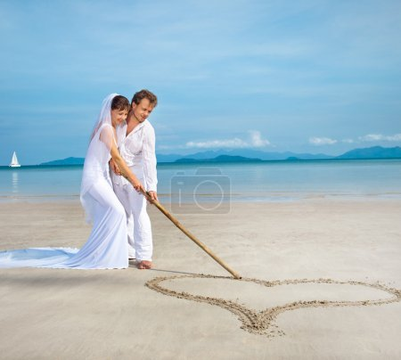 Photo for Beautiful couple on the beach in wedding dress drawing heart - Royalty Free Image