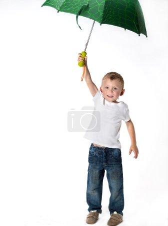 Cute boy sitting with umbrella
