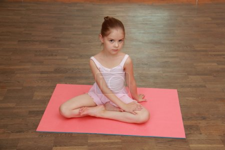 Lovely little girl doing sports exercises on the mat (stretching)
