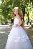 Charming young girl with long healthy hair in a beautiful white dress walking outdoors