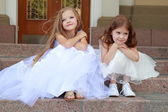 Two young girls in white wedding dresses sitting on the steps outside the building outdoors