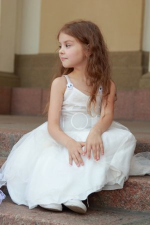 Happy smiling little girl in a white ball gown and sitting on the stairs outdoors