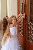 Mladá dívka v bílých svatebních šatech se snaží otevřít velké dveře do budovy venku