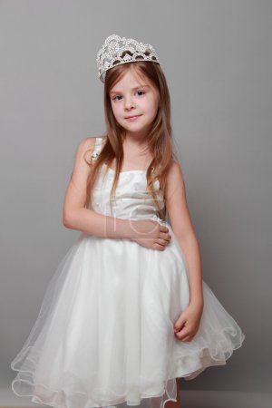 European cute young girl wearing a crown and a white dress with a cute smile on Holiday
