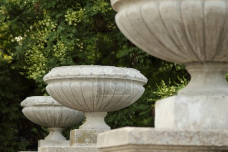 Old stone vase stands on the railing of the stairs